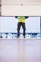 Worker lifting door in warehouse - CAIF02762