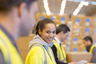 Worker smiling in warehouse - CAIF02765