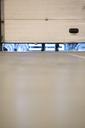 Worker lifting garage door in warehouse - CAIF02771