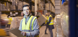 Worker using clipboard in warehouse - CAIF02780
