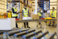 Workers checking packages on conveyor belt in warehouse - CAIF02783