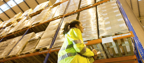 Worker writing on clipboard in warehouse - CAIF02789