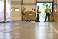 Workers talking in warehouse - CAIF02795