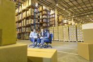 Business people talking in warehouse - CAIF02798
