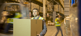 Worker carrying box in warehouse - CAIF02804