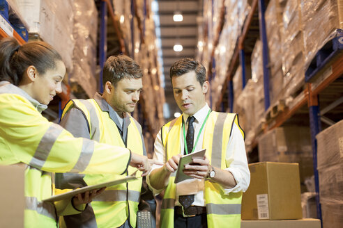 Businessman and workers talking in warehouse - CAIF02810