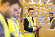 Businessman and workers in warehouse - CAIF02819