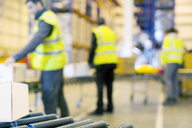 Workers examining boxes on conveyor belt in warehouse - CAIF02837