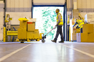Worker carting boxes in warehouse - CAIF02840