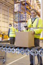 Worker scanning box on conveyor belt in warehouse - CAIF02852