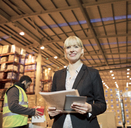 Businesswoman with folder and tablet computer in warehouse - CAIF02855