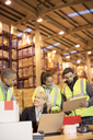 Businesswoman and workers talking in warehouse - CAIF02858