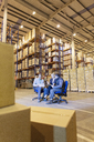 Business people talking in warehouse - CAIF02861