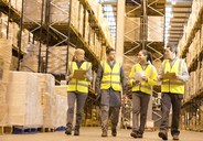 Workers talking in warehouse - CAIF02873