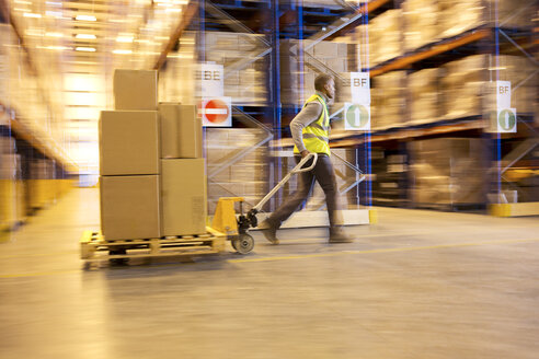 Blurred view of worker carting boxes in warehouse - CAIF02879