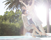 Fully dressed friends jumping into swimming pool - CAIF02894