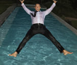 Fully dressed man jumping into swimming pool - CAIF02906