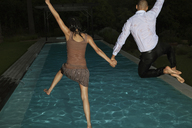 Fully dressed friends jumping into swimming pool - CAIF02924