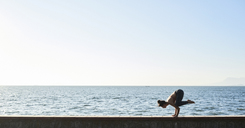 Young woman practicing yoga on a wall by the sea - IGGF00440