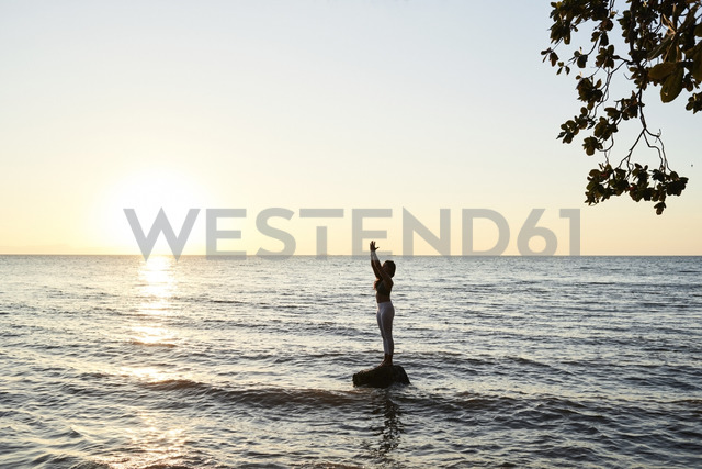 Young woman practicing yoga on a rock in the sea at sunset - IGGF00446