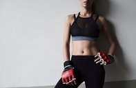 Mid-section of confident female boxer against grey wall - IGGF00465