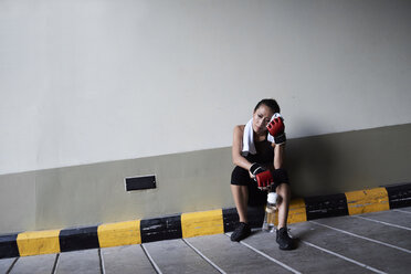 Female boxer sitting in a garage holding a towel - IGGF00468