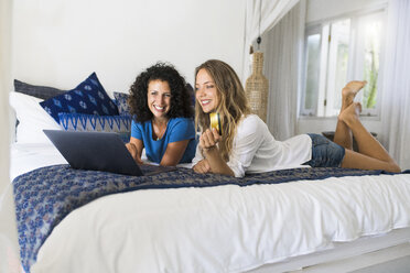 Two smiling women lying in bed shopping online with credit card and laptop - SBOF01422