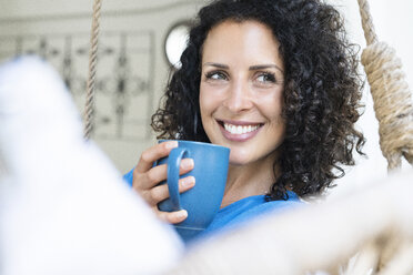 Smiling woman with curly hair holding cup of coffee - SBOF01434