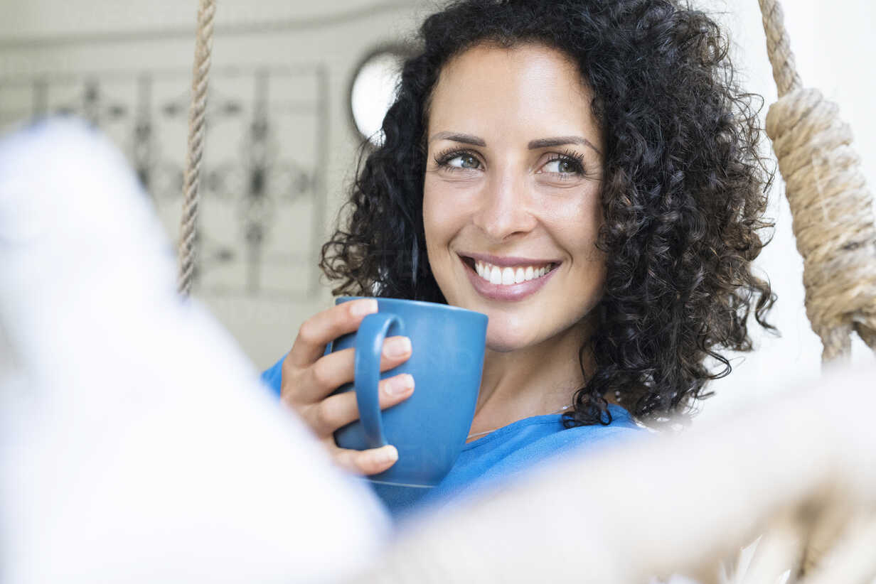 Smiling woman with curly hair holding cup of coffee - SBOF01434 - Steve Brookland/Westend61