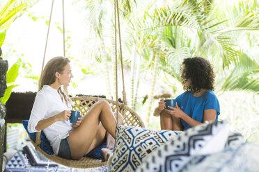 Two women talking on terrace having a cup of coffee - SBOF01437