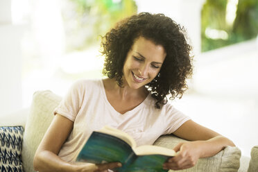 Smiling woman with curly hair reading a book - SBOF01446