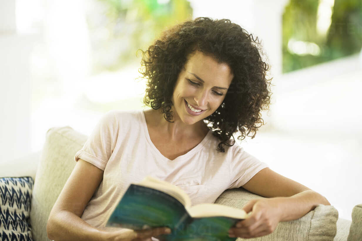 Smiling woman with curly hair reading a book - SBOF01446 - Steve Brookland/Westend61