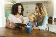 Two smiling women with a child using tablet at kitchen table - SBOF01455
