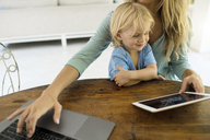 Boy sitting on his mother's lap and looking at a tablet while his mother is working on a laptop - SBOF01458