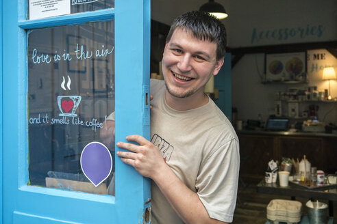 Portrait of a smiling coffee roaster on the door of a coffee roastery - TAMF00933