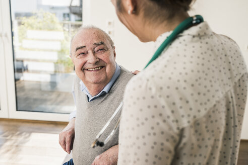 Senior man smiling at nurse at home - UUF12868