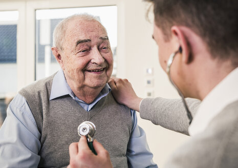 Senior man smiling at nurse with stethoscope at home - UUF12877