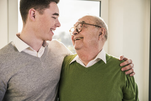 Senior man smiling at young man - UUF12892