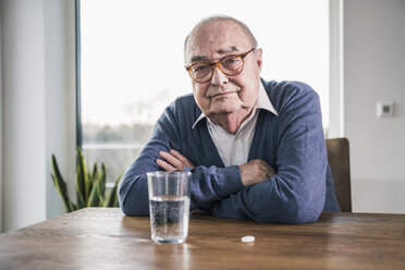 Portrait of senior man sitting at table with pill and glass of water - UUF12901