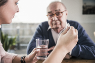 Woman holding pill and glass of water for senior man - UUF12904