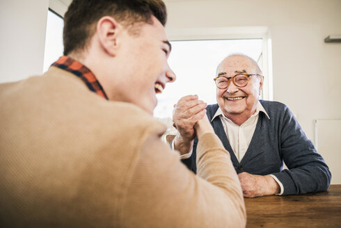 Happy senior man and young man arm wrestling - UUF12916