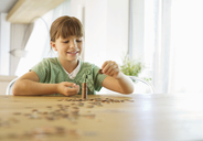 Girl stacking pennies on counter - CAIF02945