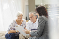 Financial advisor talking to couple on sofa - CAIF02951