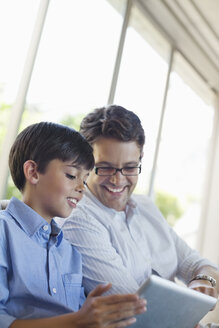 Father and son using tablet computer - CAIF02978
