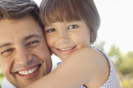 Father holding daughter outdoors - CAIF02993