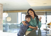 Mother and son smiling in kitchen - CAIF03008
