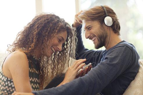 Couple listening to headphones on sofa - CAIF03059