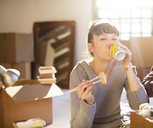 Woman drinking soda and eating sushi in new home - CAIF03101