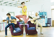 Men playing music together in living room - CAIF03107