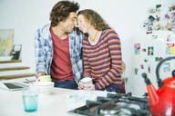 Couple relaxing together in kitchen - CAIF03113